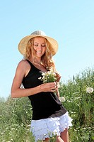 Romantic girl in the hat on the summer meadow