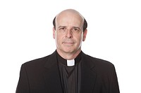 Studio portrait of mature bald Caucasian priest looking serious on white background