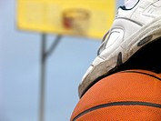 A foot on top of a basketball with out_of_focus hoop in background.