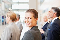 Portrait of smiling businesswoman in lobby with co_workers