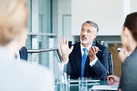 Gesturing businessman leading meeting in conference room (thumbnail)