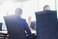 Businessmen meeting in sunny conference room