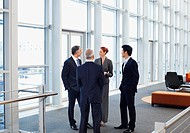 Business people meeting at window in office lobby (thumbnail)