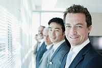 Portrait of smiling business people standing in a row at window