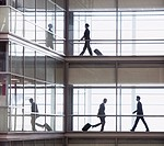 Businessmen walking along corridor in modern office