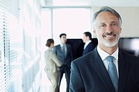 Portrait of smiling businessman with co_workers in background