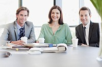 Portrait of smiling business people with coffee at table