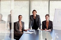 Portrait of smiling businesswomen at table in conference room
