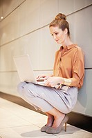 Smiling businesswoman using laptop in corridor