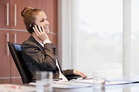 Smiling businesswoman talking on cell phone at desk in office (thumbnail)