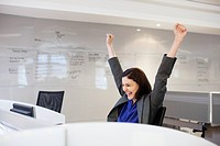 Enthusiastic businesswoman with arms raised in office (thumbnail)