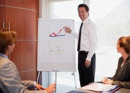 Businessman pointing to flipchart in conference room (thumbnail)