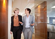 Businesswomen talking and walking in office corridor