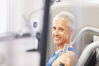 Portrait of smiling man using exercise machine in gymnasium