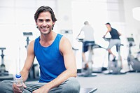 Portrait of smiling man sitting on exercise mat in gymnasium