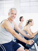 Portrait of smiling man on exercise bike in gymnasium