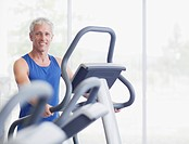 Portrait of smiling man on elliptical machine in gymnasium