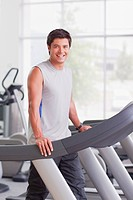 Portrait of smiling man walking on treadmill in gymnasium