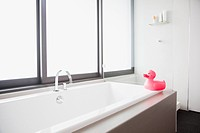 Pink rubber duck at edge of bathtub in modern bathroom