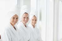 Portrait of smiling women in bathrobes and hair wrapped in towels at spa