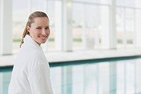 Portrait of smiling woman in bathrobe at poolside