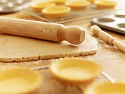 Rolling pin on dough surrounded by puff pastry tarts
