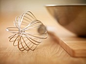 Close up of wire whisk and metal mixing bowl