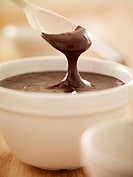 Spoon scooping melted chocolate from bowl