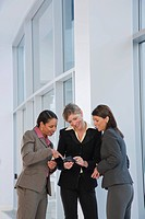 Three businesswomen text messaging on a mobile phone