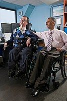 Two businessmen in an office, one with muscular dystrophy and breathing ventilator and another with spinal cord injury