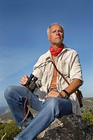 Mature man explorer posing outdoors with is binoculars