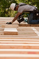 Carpenter using a nail gun at a construction site