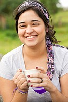 Smiling Hispanic woman drinking coffee