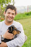 Smiling Hispanic man holding dog