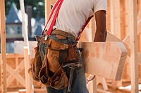 Mid section view of a carpenter carrying a wooden rafter