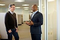 Smiling businessmen talking together in office