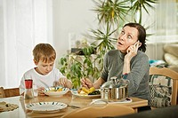 Mother speaking on the phone, sitting at the table with her son