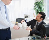 Businessman bringing coffee to co_worker