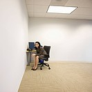 mixed race businesswoman sitting at desk in corner of office
