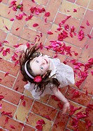 Little girl, three years, dancing on red petals, from above