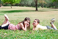 Cute children lie down on green grass and looking eachother in the park, outdoor