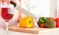 Woman cutting a pepper in a kitchen
