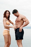Couple laughing happy in bathing suits. girl is rubbing off sand of his abs.