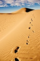 footprints on desert sand dunes with cloudy blue sky