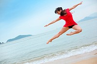 Beautiful young woman dancing on beach