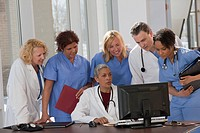 Doctors and nurses consulting on a computer in hospital