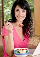 beautiful smiling woman in pink top, sitting in her home having breakfast