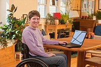 Woman with multiple sclerosis using a laptop in her accessible home