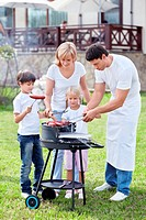 Happy family cooks sausages outdoors