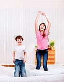 Two kids jumping on bed